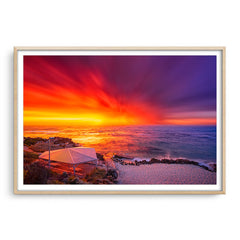 An explosive sunset over Mettams Pool in Perth, Western Australia framed in raw oak