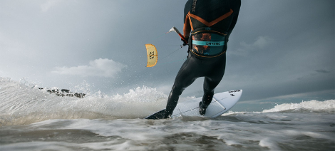 Male kitesurfer wearing harness in choppy water