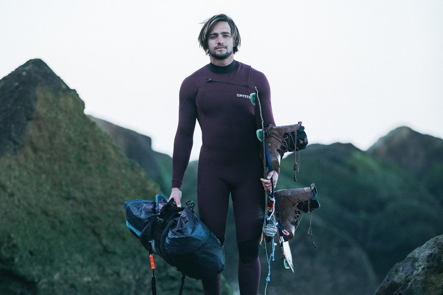 A male model wearing the 2021 Mystic Marshall 5/3 winter wetsuit and facing the camera, cliffs in background