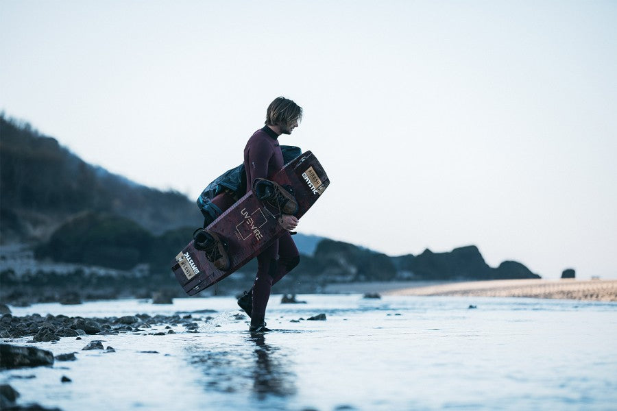A male model wearing the 2021 Mystic Marshall 5/3 winter wetsuit, carrying a kitesurfing board and bag and walking in the water