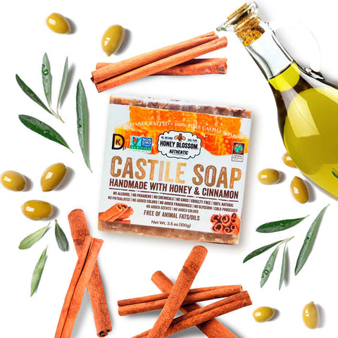100% Castile Soap on a white surface, with olives, a bottle of olive oil and cinnamon sticks around it.