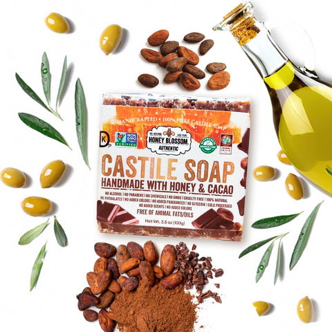 Image of 100% Castile Soap on a white surface, with olives, a bottle of olive oil and cacao beans around it.