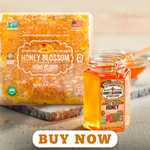 """a jar of Jungle Blossom honey, with a USA Honeycomb on the back, on a wooden table, with a warm light. And a button that says """"Buy Now""""."""