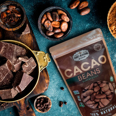 Honey Blossom's bag of Cacao Beans, on a blue dark table, with plates full of cacao beans, another of chocolate pieces and another of chocolate chips