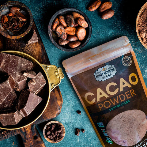 Image of the bag of cacao, on a wooden table with blue paint, and several bowls with cacao beans and cacao nibs.