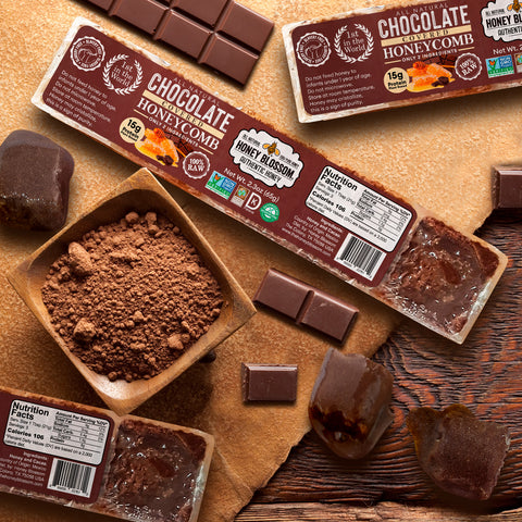 2 Chocolate Covered 100% RAW Honeycomb Snack Size, 5 Servings on a wooden table, with a jar with cacao powder, chocolate bars on their sides along with cubes of honeycomb with chocolate
