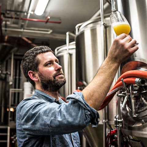 a brewer in his brewery, checking a glass of beer.