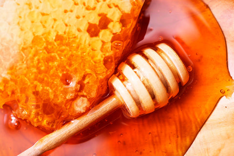 a honeycomb dripping honey and a dipper stick next to it
