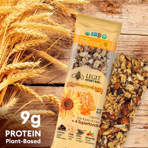 Image of Sunflower Honey Snack Bar, with its unwrapped bar, on a rustic wooden table, and ripe oats to its left. And text that says: 9g protein plant based
