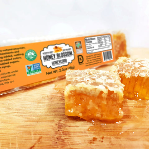 Image of Raw honeycomb Snack size, 5 servings on a wooden board with 2 honeycomb cubes cut in front of it, with honey falling from them