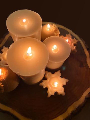 Photo of 3 large candles, 2 sphere-shaped candles and 3 snowflake-shaped candles, all lit and colored yellow, on a log at night.