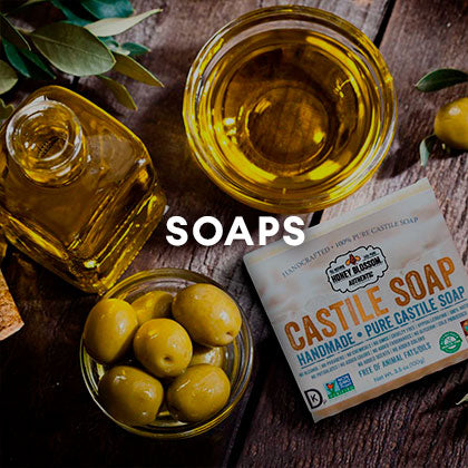 Picture of the soap on a rustic wooden table, with a bowl with olives, a bowl with olive oil and a bottle full of olive oil. And a title that says: Soaps