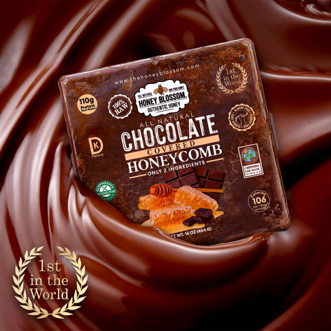 """Image of Chocolate Covered Honeycomb dropping into melted chocolate. And on the bottom the """"First in the world"""" logo with laurel leaves around it."""