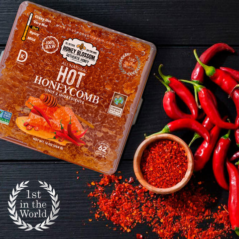 """100% RAW Hot Honeycomb, on a dark-colored wooden table, with hot peppers on the right, and the """"First in the world"""" logo with laurel leaves around it."""
