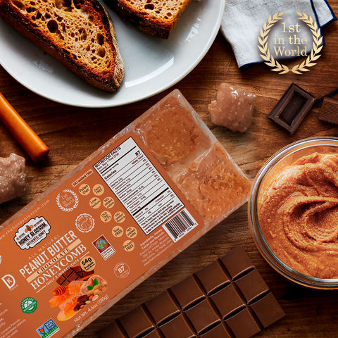 the Peanut Butter Chocolate Covered 100% RAW Honeycomb Snack Size, 10 Servings on a wooden table with a jar of peanut butter and chocolate bars next to it, a plate with toasted bread on top and cubes of honeycomb with peanut butter and chocolate
