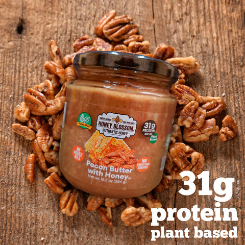 the pecan butter with honey jar on a pile of pecans, on a wooden table and text that says: 31g protein plant based