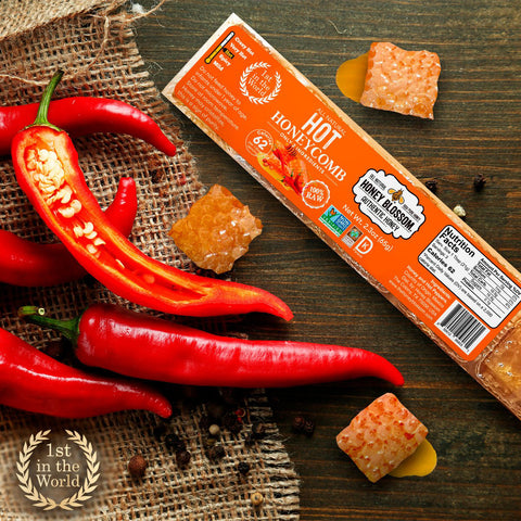 """RAW Hot Honeycomb Snack Size, 5 Servings, on a dark-colored wooden table, with hot peppers on the right, and the """"First in the world"""" logo with laurel leaves around it."""