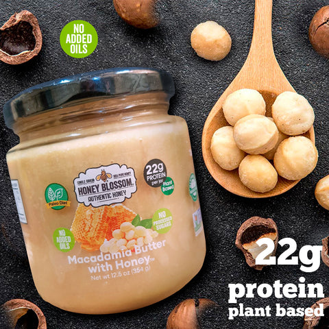 """Image of the jar, on a graphite table, with many macadamias around it, as well as a spoon full of peeled macadamias, a logo that says """"No added oils"""" and text that says: 22g protein plant-based"""