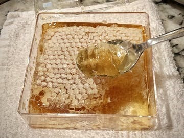 Photo taken by customer showing Honey Blossom honeycomb box opened, with a spoon cutting a piece of it.