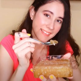 Image of a girl smiling at the camera while eating Honey Blossom honeycomb, straight from the box.