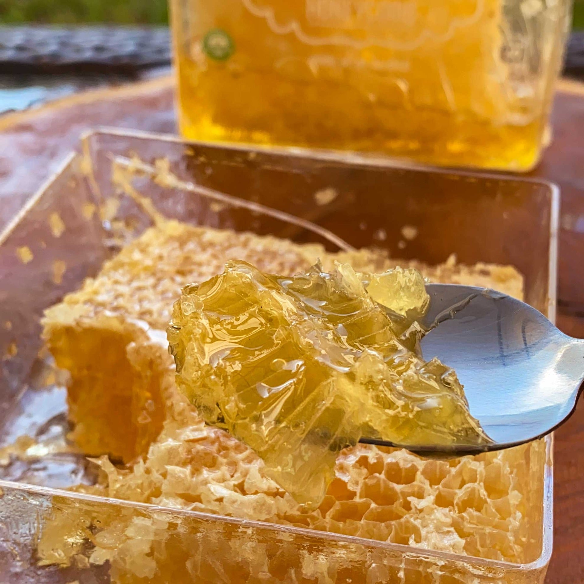 Image of the open USA Honeycomb box, with a spoon showing a cut piece of the honeycomb.