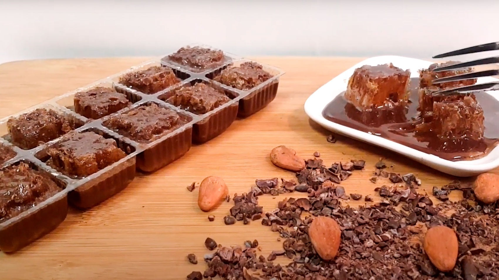 Video of the Chocolate Covered 100% RAW Honeycomb Snack Size, 10 Servings, open on a wooden board, with cacao beans and chocolate chips, and a dish with chocolate honeycomb cubes being cut by a fork