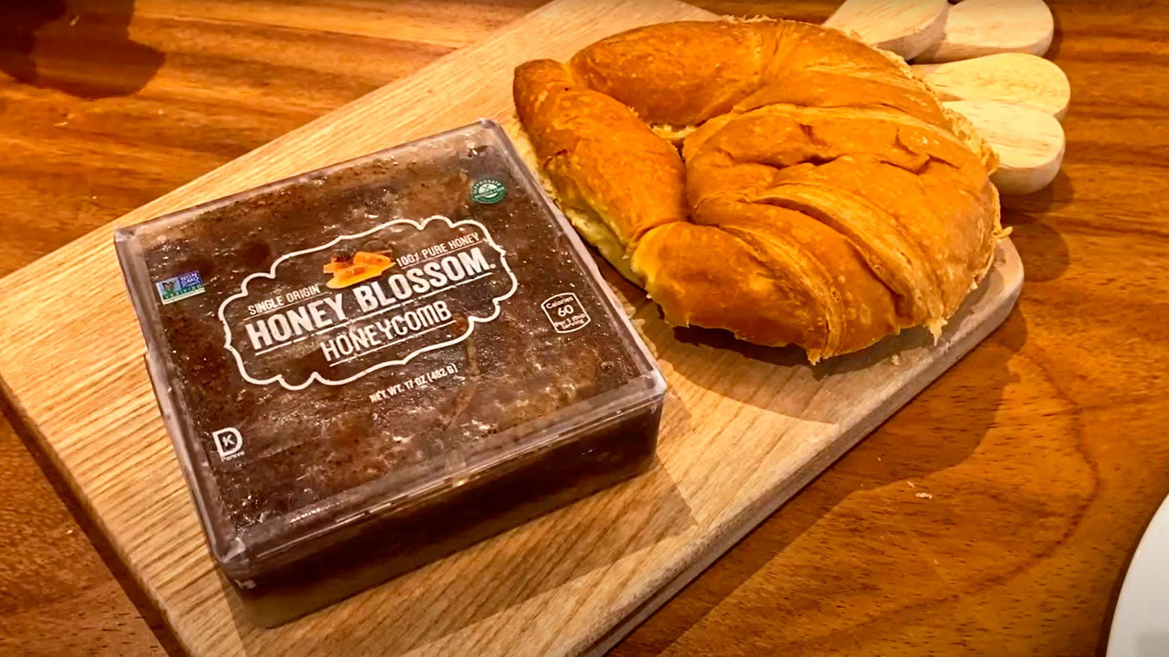 Video with Honey Blossom's Chocolate Covered Honeycomb box, being opened and cut with a knife, and pouring the honeycomb into a large horn bread, on a wooden board, on a wooden table.