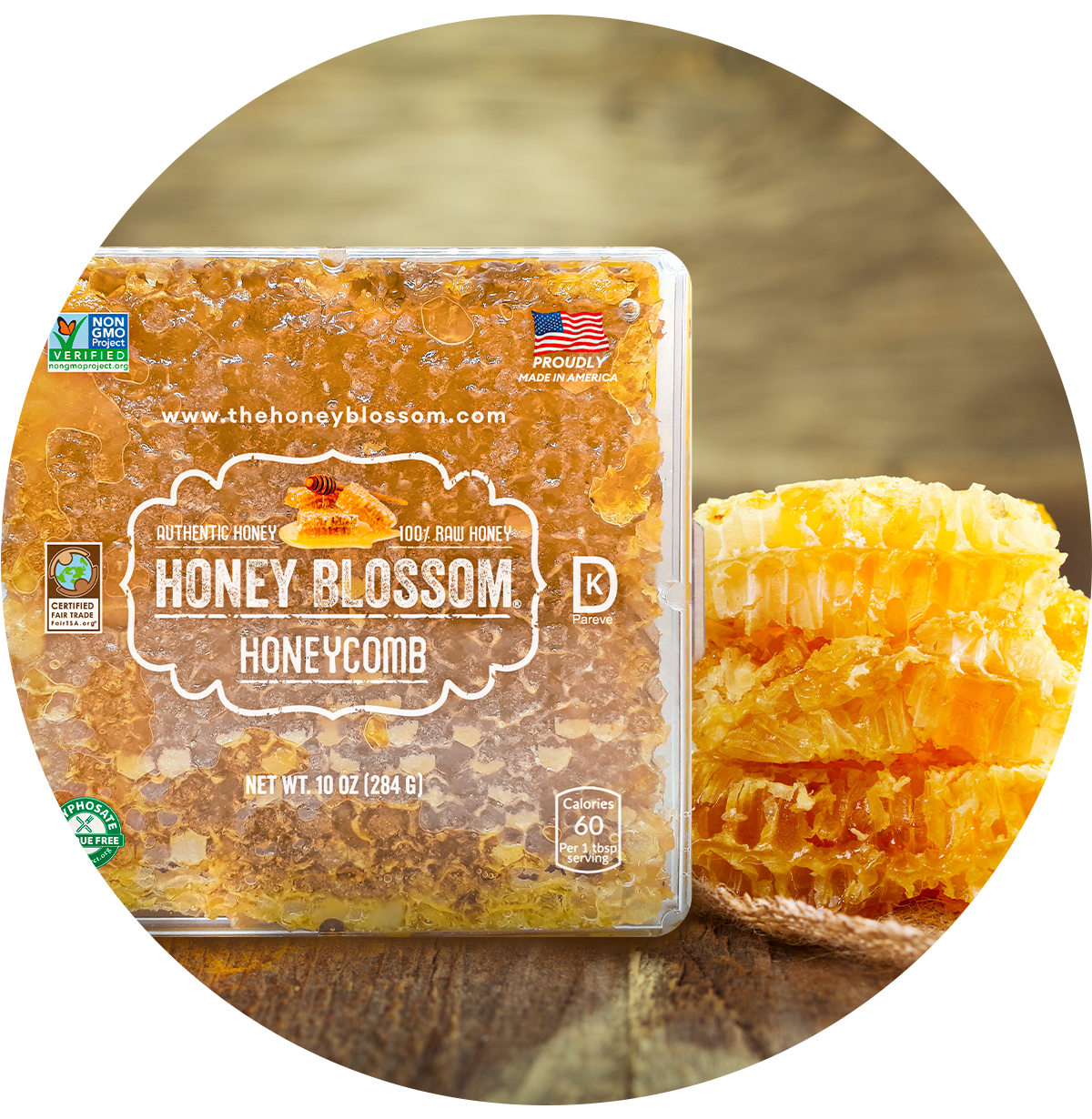 Image of Honey Blossom honeycomb box on a wooden table, and 2 honeycombs behind it.