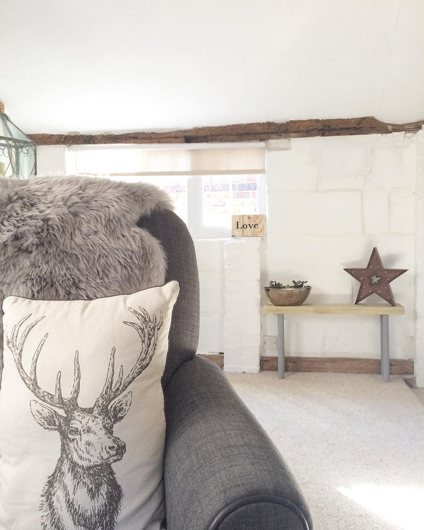 Living room armchair with a stag cushion: would you renovate a listed property? Amanda did. Find out how she got in here on www.lovetohome.co.uk - Photo credit: with permission from @theoldforgecottage