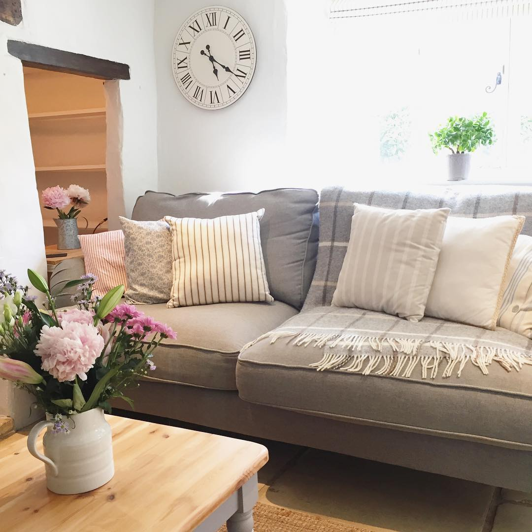 This classic country cottage with a woodburner and grey sofa is just beautiful, don't you think? See the full home tour on www.lovetohome.co.uk