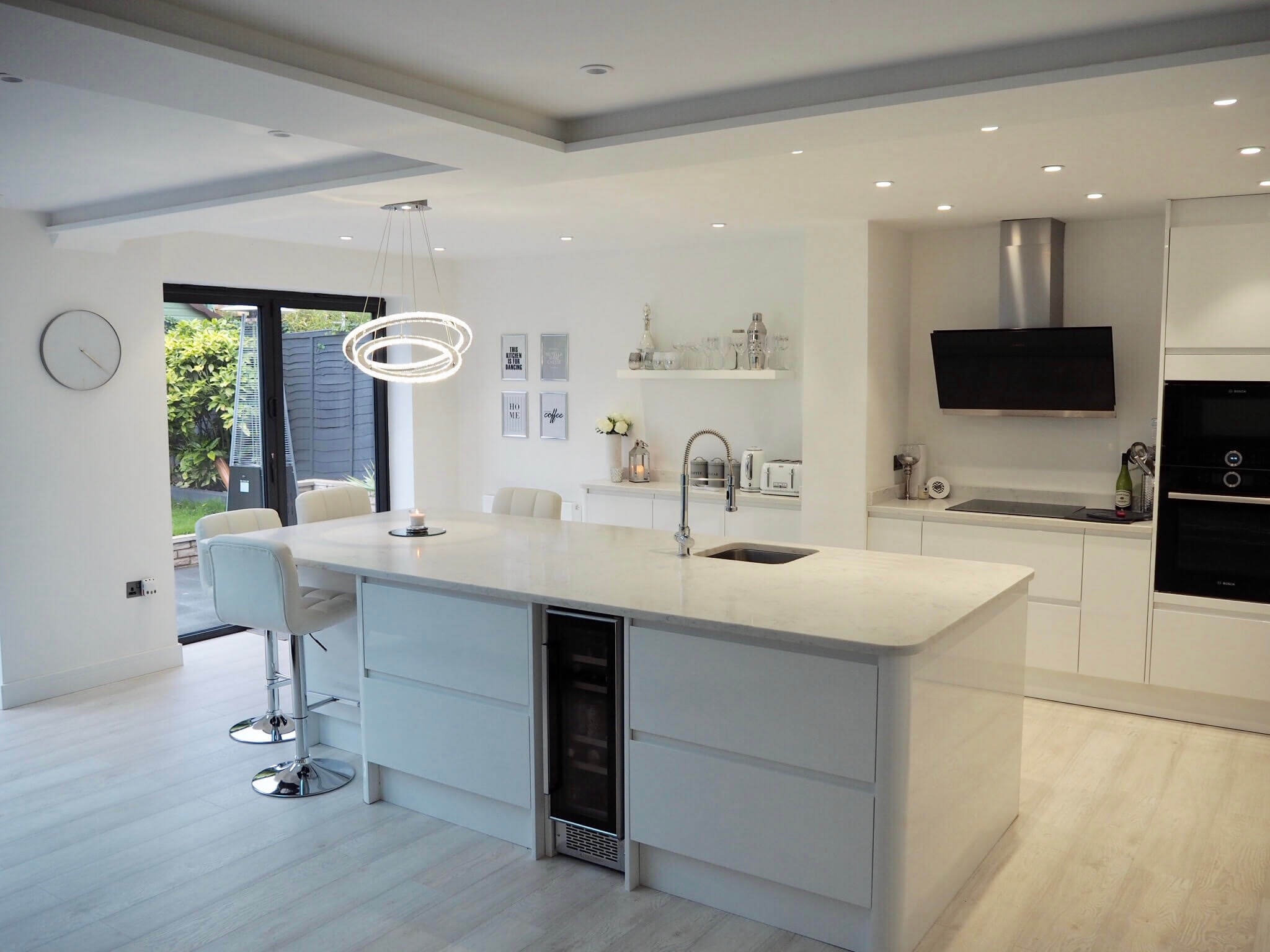 A white, bright and modern contemporary kitchen with bifolding doors.