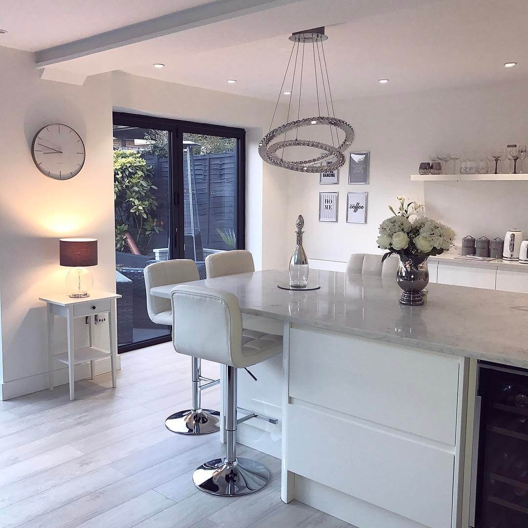 Softly lit Scandinavian inspired white modern contemporary open plan kitchen living room with bi folding doors.