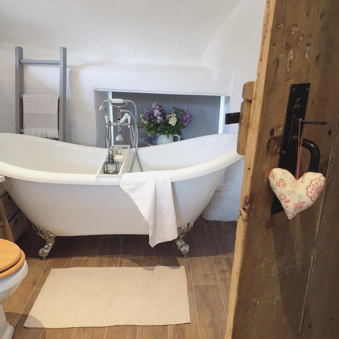 Isn't this traditional white country cottage bathroom perfect with its roll top bath? See the full home tour on www.lovetohome.co.uk