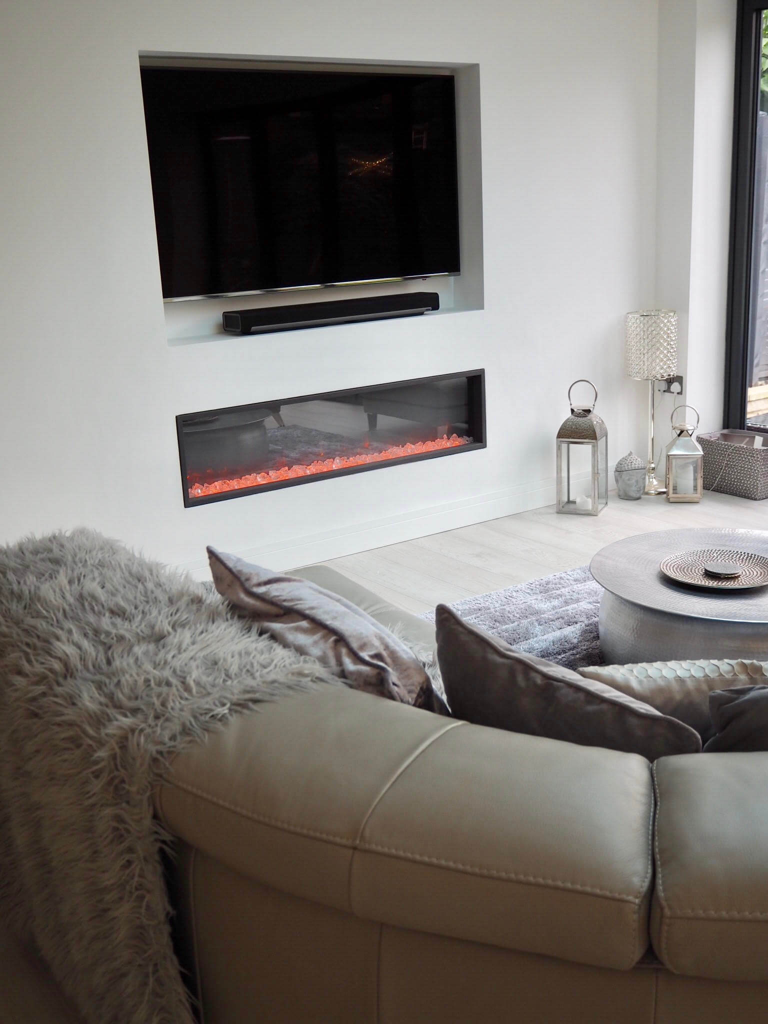 A cosy corner of a Scandinavian inspired white modern contemporary open plan kitchen living room with bi folding doors.