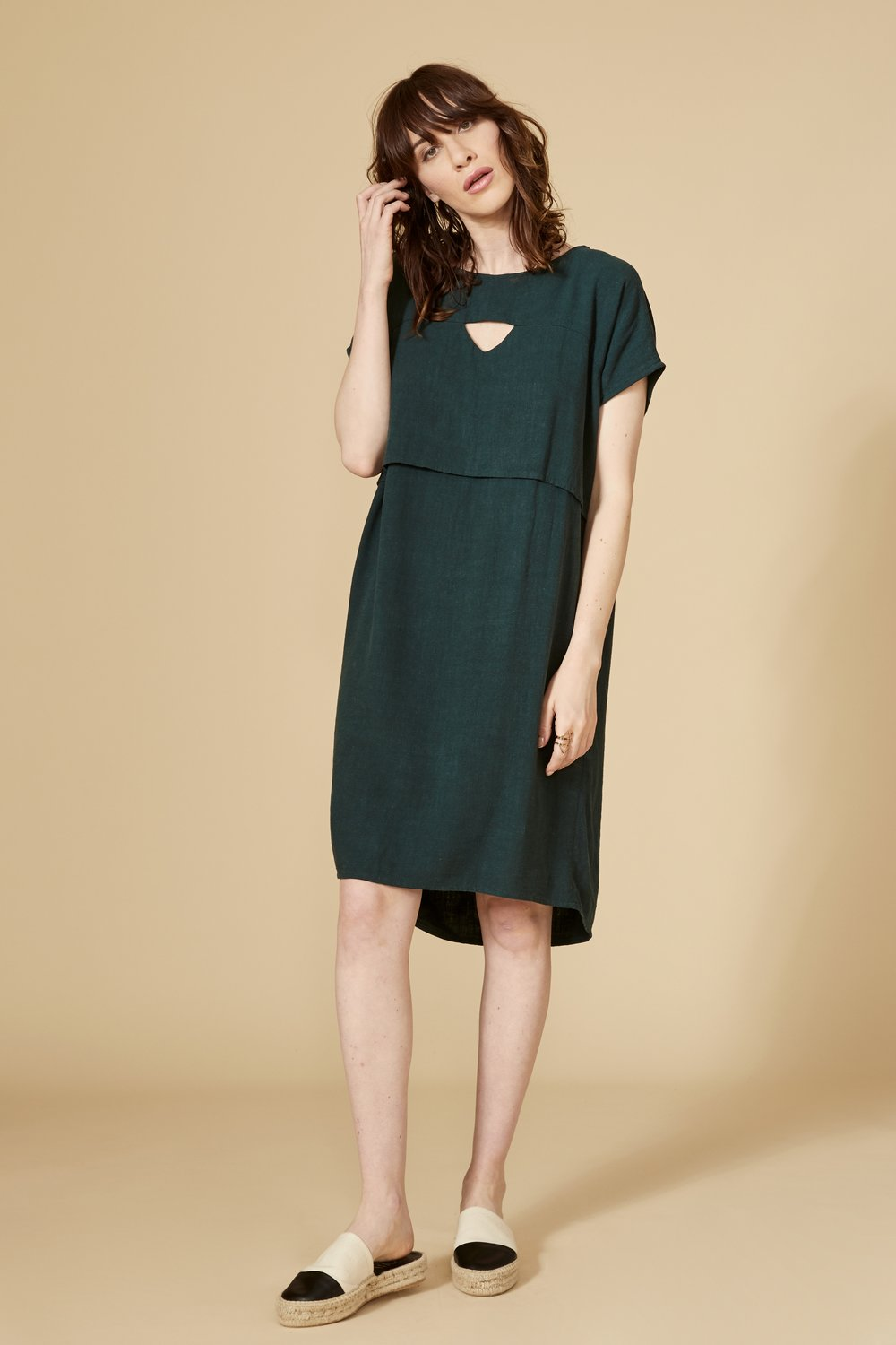 Teal cut-out dress with short sleeve, round collar and slightly longer at the back. 70% viscose, 30% linen. Hand wash in cold water, air dry flat. Designed and Made in Montréal.