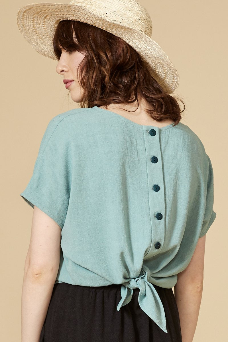 Aqua reversible top with short sleeves. The buttoned side can be worn in front and behind. Round neckline.  70% viscose, 30% linen. Hand wash in cold water, air dry flat. Designed and Made in Montréal.