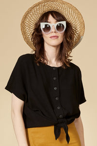 Black reversible top with short sleeves. The buttoned side can be worn in front and behind. Round neckline.  70% viscose, 30% linen. Hand wash in cold water, air dry flat. Designed and Made in Montréal.