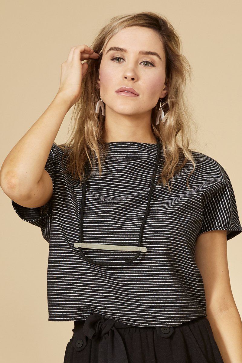 Black stripe reversible top with short sleeves. The buttoned side can be worn in front and behind. Round neckline.  70% viscose, 30% linen. Hand wash in cold water, air dry flat. Designed and Made in Montréal.