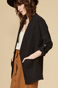 Black mid-length oversize jacket with 3/4 fold-out sleeves. Attaches in front with a button. Large side pockets. 70% cotton, 30% linen Hand wash in cold water, air dry flat. Designed and Made in Montréal.