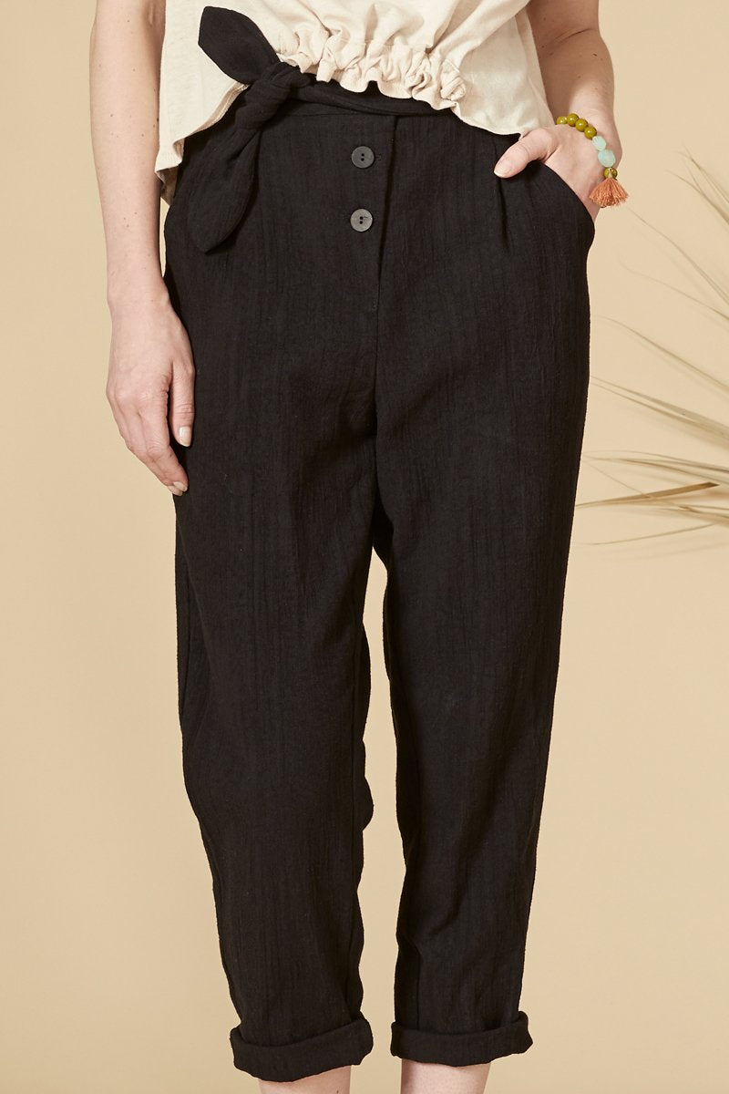 Black mid-calf length pants with fabric belt at the waist. Buttons in front, high waist, Side pockets. 70% cotton, 30% linen. Hand wash in cold water, air dry flat. Designed and Made in Montréal.