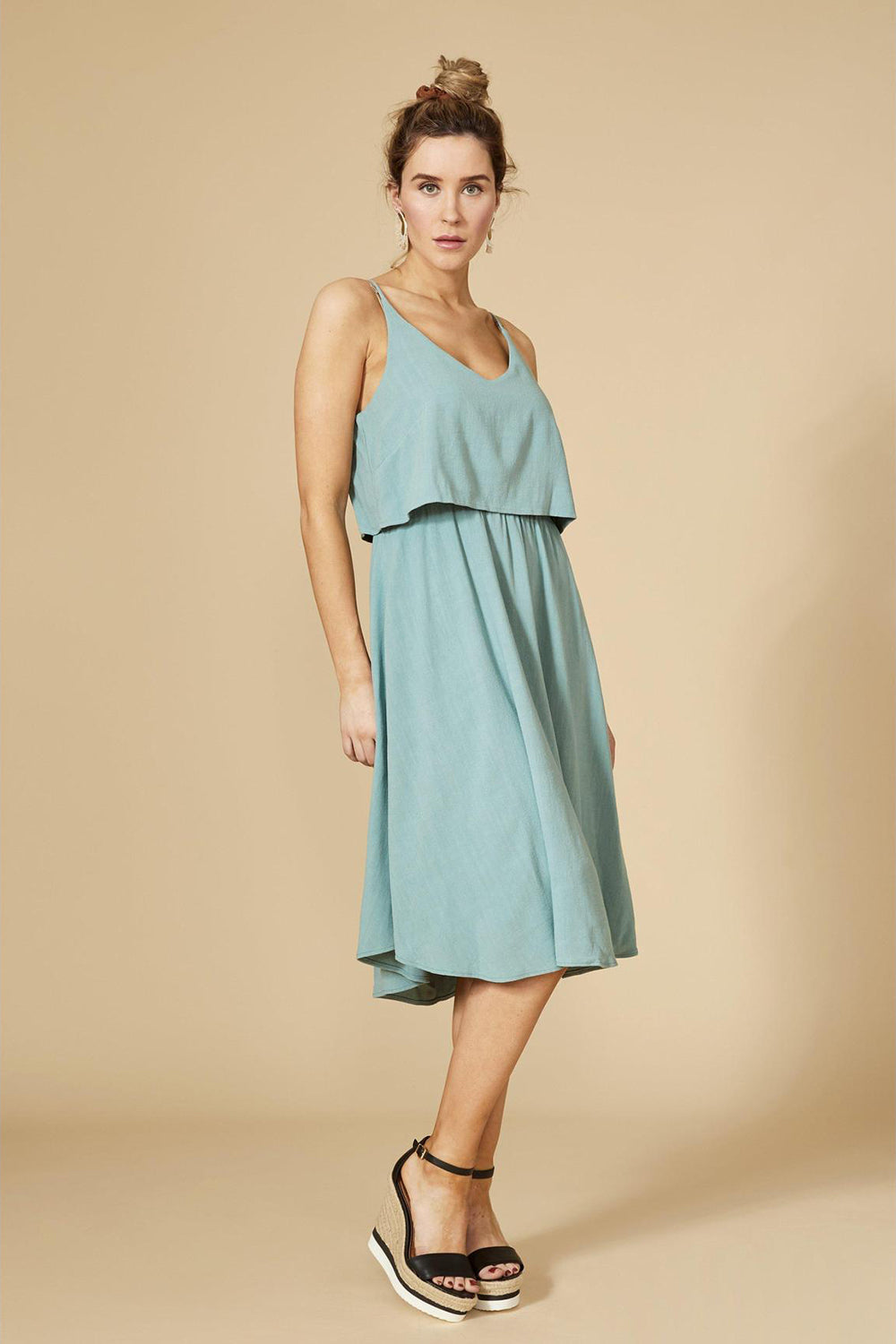 Aqua dress with spaghetti straps and rounded v-neck, knee length, with fluid cut. 70% cotton, 30% linen. Hand wash in cold water, air dry flat. Designed and Made in Montréal.