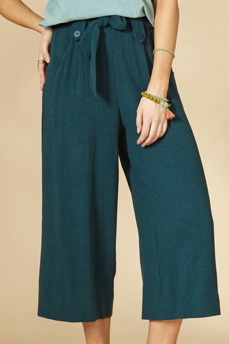 Teal 7/8 pants, with a high waist, side pockets, fabric belt at the waist, and wide leg. 70% viscose, 30% linen. Hand wash in cold water, air dry flat. Designed and Made in Montréal.
