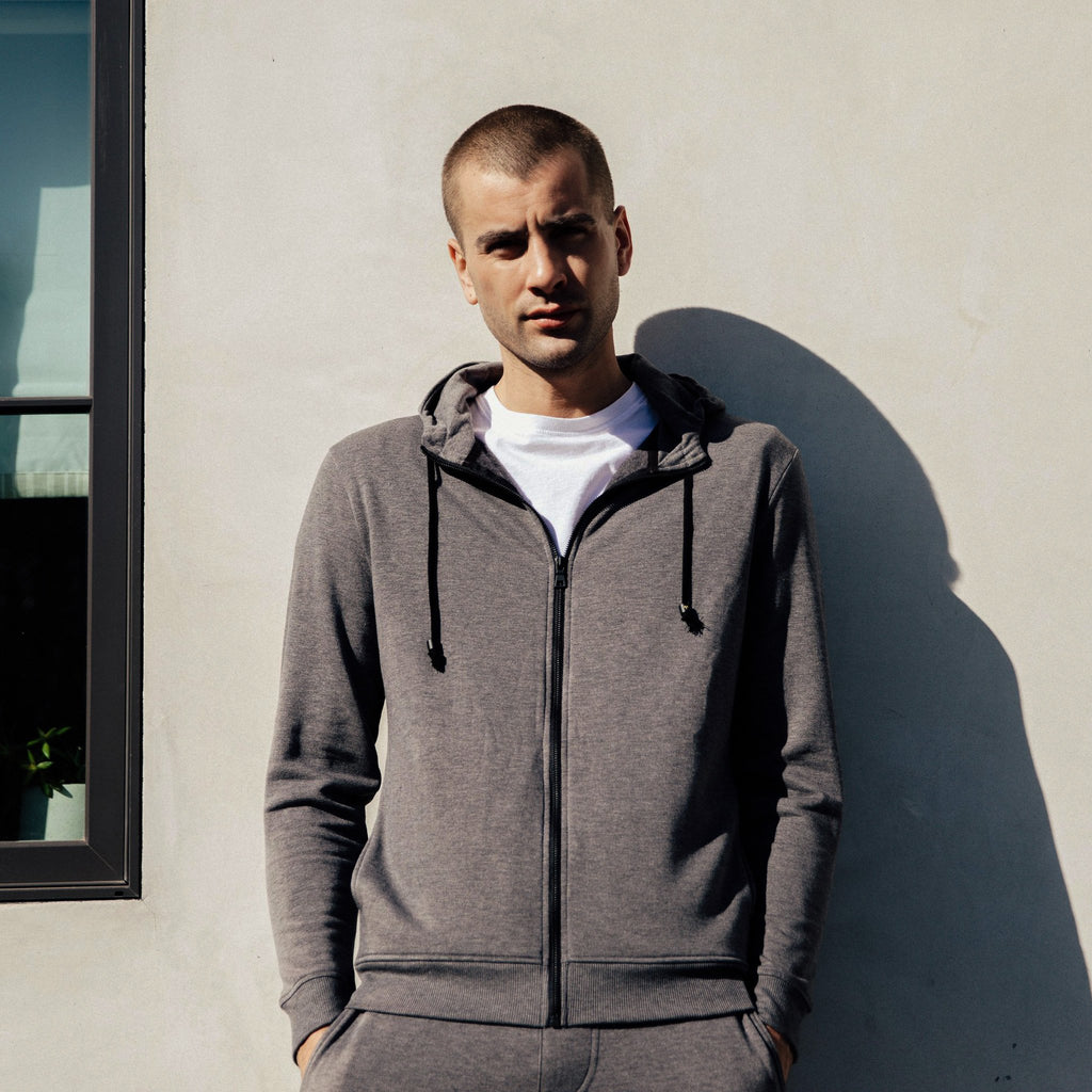 Alright now, this is a hoodie, the Mercer by Mitchell Evan in grey. This zip-up closet staple is made of signature brush luxe fleece fabric. The Japanese drawcord and matte black zipper pull give it unique details in the world of hoodie aficionados. Body: 61% Poly, 34% Rayon, 5% Spandex. Rib: 62% Poly, 33% Rayon, 5% Spandex. Machine wash cold, delicate cycle, line dry. Made in America, 100% in Los Angeles.