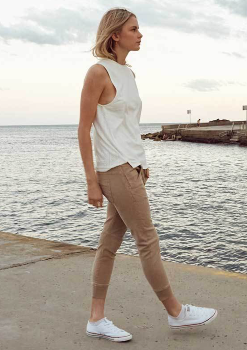 Dricoper Active Jogger Jean - Sand  Active Beach Sand Jeans are a mid rise relaxed fit with elasticated waistband and sportive draw string. Scooped Front Pockets and an arched shape leg gives it a flattering look. These super comfy jeans with cuffed bottom look great paired with sneakers or heels. The slight distress front and the worn out look is done by hand scraping.