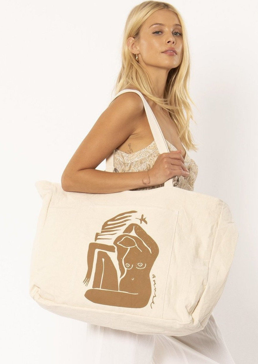 Large oversized beige canvas totel. An island muse graphic covers the front and shoulder straps feature tortoise shell ring details.