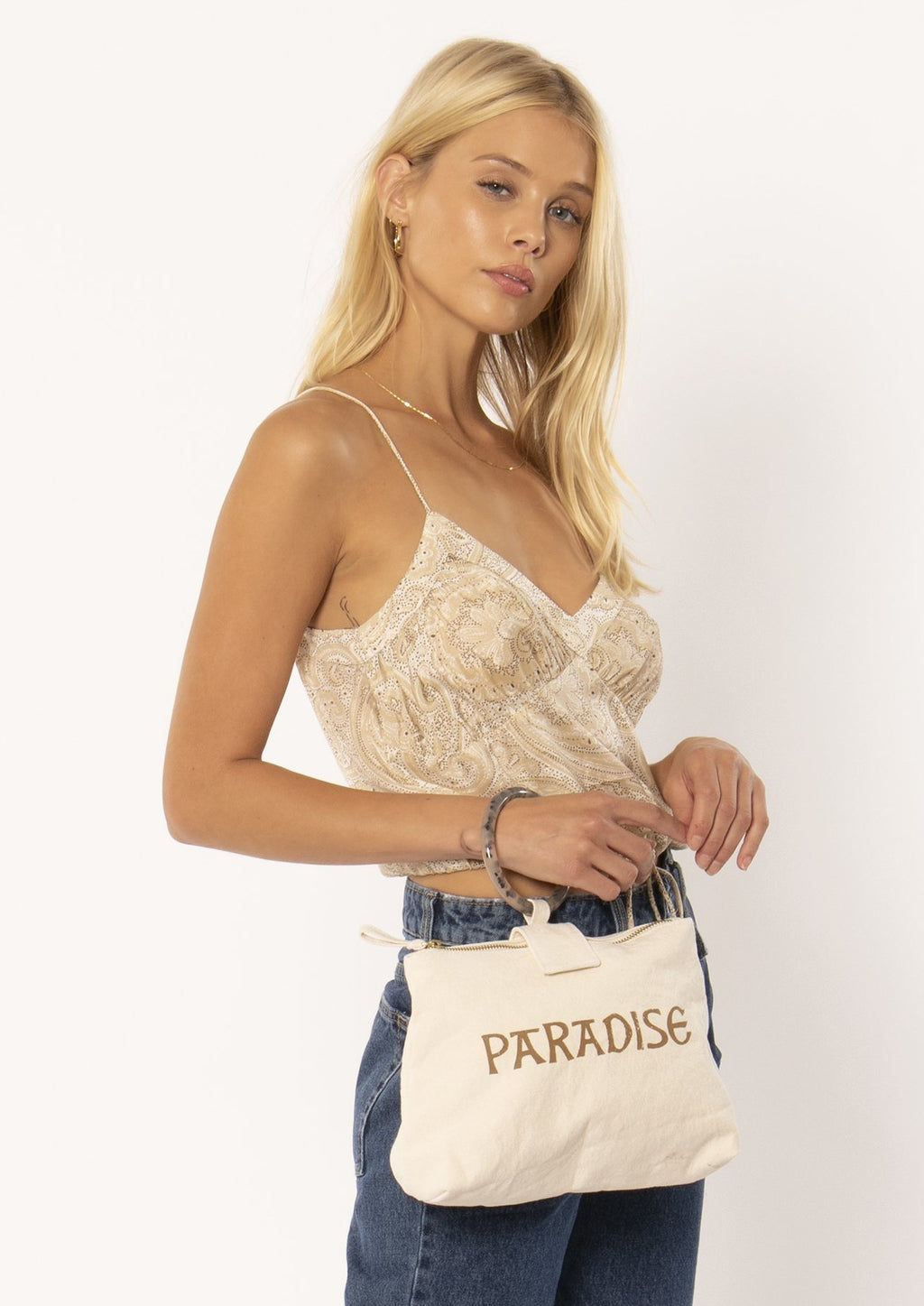 The zip-top bag features large wrist sized tortoise shell ring to make carrying easy and chic.