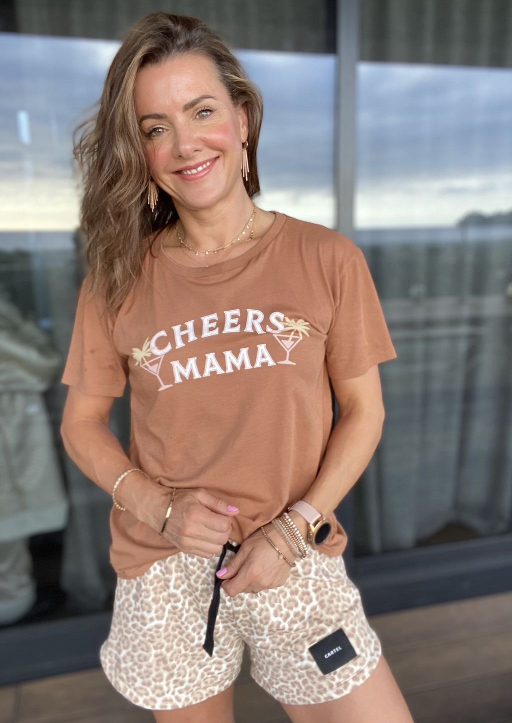 Cheers Mama Tee - Smoke  The cutest relaxed fit tee with the universal saying, Cheers Mama!  Details:  100% Cotton  *Turn garment inside out before machine wash cold separately  *Tumble dry low