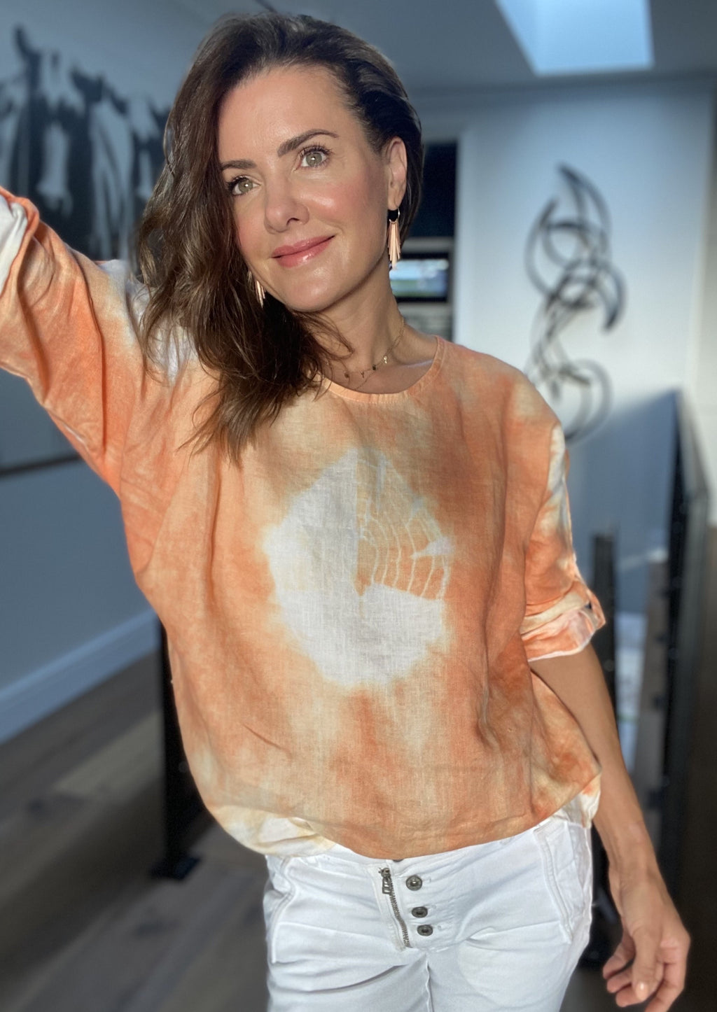 Everything to Me Top - Orange, by Ridley the Label  This modern 100% Linen Top features a unique tie dye effect in fresh orange and white to pair back beautifully with your white pants and jeans, and light denims.  Features:  Relaxed fit  Scoop neck  7/8th sleeves with button tab so it can be rolled and worn as a short sleeve  Rounded hemline  Made in Italy