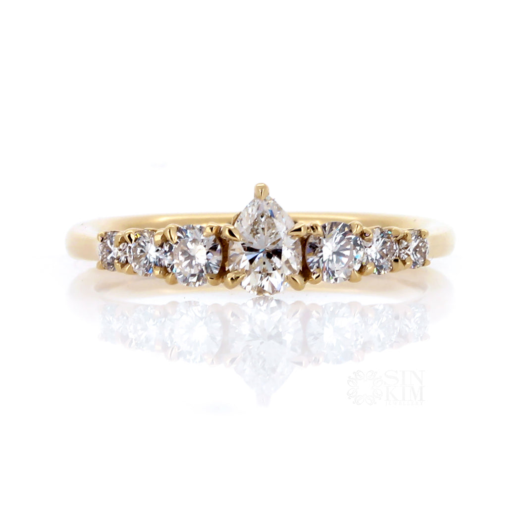 Pear  shape centre stone flanked by tapering sized round brilliant cut diamonds, set in 14k yellow gold.