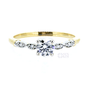 0.50ct round diamond, set in a vintage inspired, white and yellow gold,  two-toned, engagement ring.  This ring is accented with delicate, white gold, diamond pavéd petals, and four, tiger claw, centre setting.